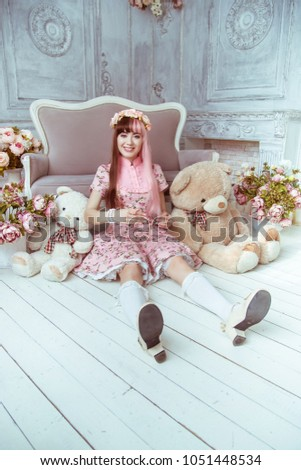 Stock Photo Beautiful young woman doll in a pink dress in a room with flowers, sits on the floor with other toys and plush bear, lolita. Japanese street fashion.