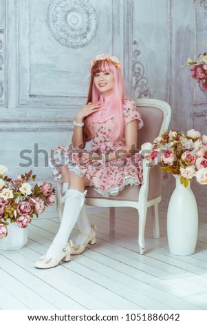 Stock Photo Beautiful young woman doll in a pink dress in a room with flowers, sitting on a chair by the fireplace, lolita. Japanese street fashion.