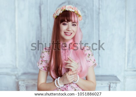 Stock Photo Beautiful young woman doll in a pink dress, with a lollipop, lolita. Japanese street fashion. Portrait.