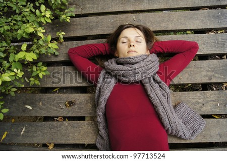 Beautiful young woman dreaming on a wooden bridge
