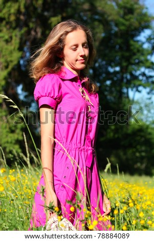 Beautiful young woman dreams. Walking in a meadow full of flowers