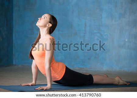 Beautiful young woman dressed in bright sportswear exercising indoors. Yogi girl working out in grunge interior with blue wall. Standing in upward-facing dog pose. Full length. Side view