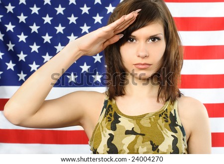 beautiful young woman dressed in camouflage stands near the American flag and salutes