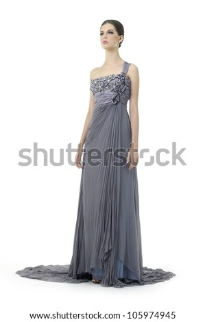 Beautiful young woman dressed in evening gown isolated over white background