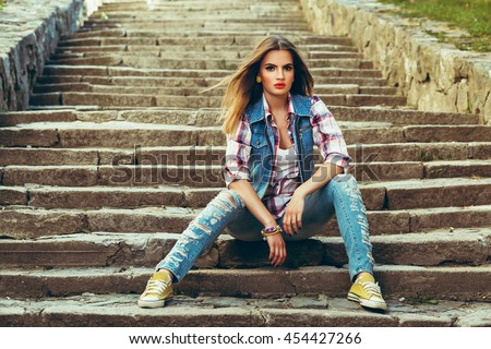 Beautiful young woman dressed in jeans posing on a concrete staircase #454427266