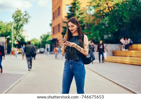 Beautiful young woman dressed in trendy clothes checking notification on smartphone while having summer walk outdoors.Pretty pensive hipster girl strolling at street and sending messages on cellular #746675653