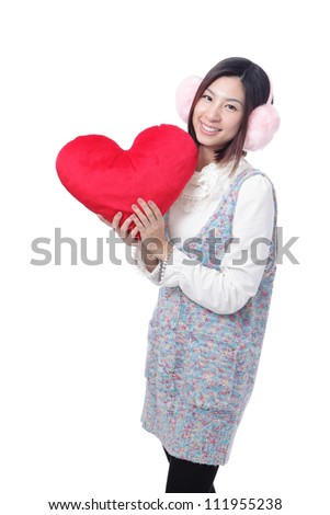 Beautiful young woman dressed in winter / autumn clothes with red heart-shaped pillow isolated on white background, model is a asian girl