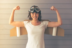 Beautiful young woman dressed like a pilot with toy wings is showing her muscles, smiling and looking upward, against gray wall