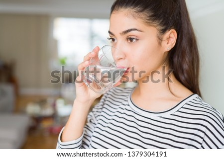 Photo of Beautiful young woman drinking a fresh glass of water at home