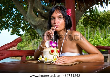 Beautiful young woman drinking cocktail outdoors