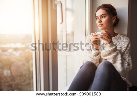 Beautiful young woman drinking coffee and looking through window while sitting at windowsill at home