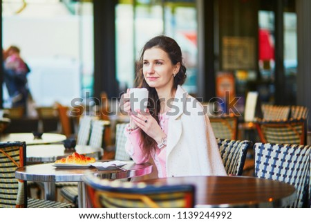 Beautiful young woman drinking coffee in outdoor cafe or restaurant, Paris, France #1139244992