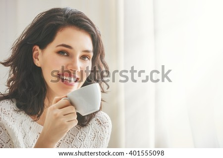 Beautiful young woman drinking coffee sitting by the window in the house.