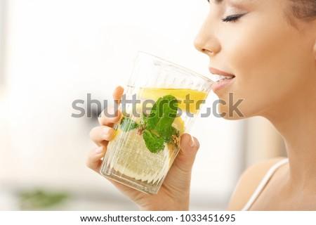 Beautiful young woman drinking fresh lemonade at home, closeup