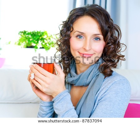 Beautiful Young Woman drinking hot tea