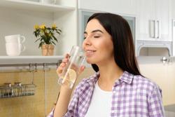 Beautiful young woman drinking lemon water in kitchen