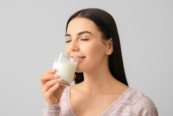 Beautiful young woman drinking milk on light background