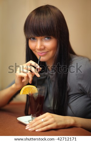 Beautiful young woman drinking mulled wine.