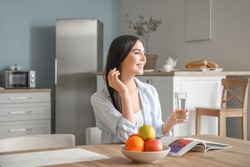 Beautiful young woman drinking water in kitchen