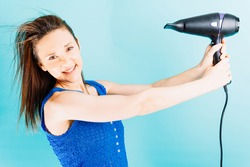 Beautiful young woman drying her hair smiling with blue background. hair care concept