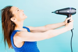 Beautiful young woman drying her hair with blow dryer smiling with blue background. hair care concept