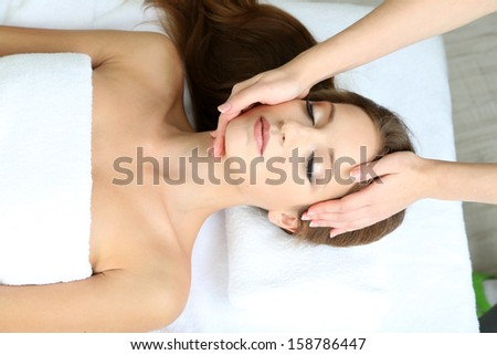 Beautiful young woman during facial massage in cosmetic salon close up #158786447