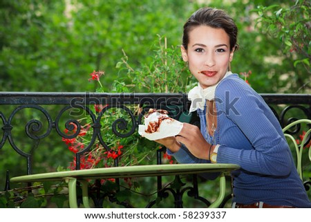 Beautiful Young Woman eating a chocolate crepe on a balcony in Paris.
