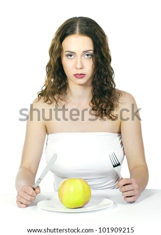 Beautiful young woman eating an apple at table on white background