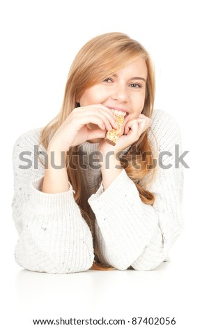 beautiful young woman eating bar with cereals, white background