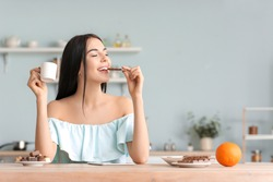 Beautiful young woman eating chocolate in kitchen