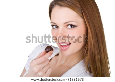 Beautiful young woman eating chocolates, isolated on white background