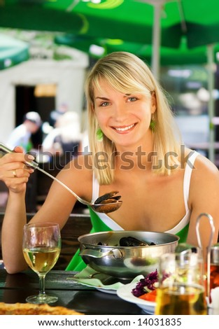 Beautiful young woman eating seafood in a restaurant