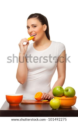 Beautiful young woman eating segments of an orange  on white background