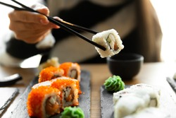 Beautiful young woman eating sushi roll at cafe. Woman eating sushi set with chopsticks on restaurant.