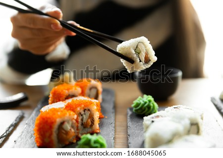 Beautiful young woman eating sushi roll at cafe. Woman eating sushi set with chopsticks on restaurant. Stok fotoğraf ©