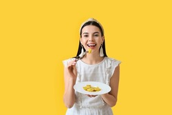 Beautiful young woman eating tasty ravioli on color background