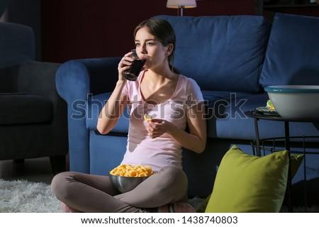 Beautiful young woman eating unhealthy food at night #1438740803