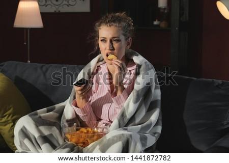 Beautiful young woman eating unhealthy food while watching TV at night Сток-фото ©