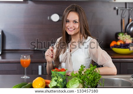 Beautiful, young woman eats salad in the domestic kitchen