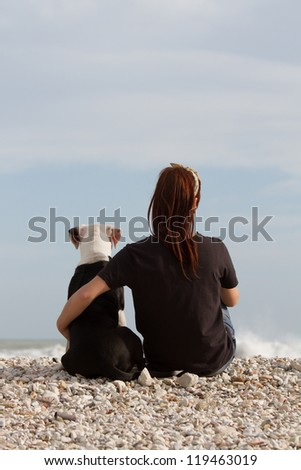 beautiful young woman embracing her dog looking at the sea