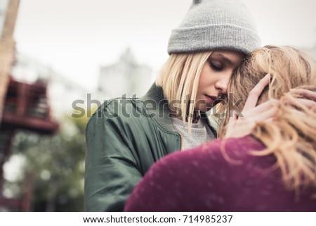 beautiful young woman embracing her sitting boyfriend