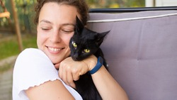 Beautiful young woman enjoying a cuddle with her black cat, hugging lovely pet, wearing white t-shirt, sitting on sofa at home terrace outdoors. Unconditional love and awe for animals. Real emotion