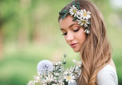 Beautiful young woman enjoying a field of daisies, attractive girl relaxing outdoors, having fun, holding bouquet of daisies, happy young lady and spring-green nature, harmony concept.