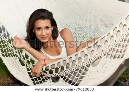 Beautiful young woman enjoying a hammock in South Beach in Miami.