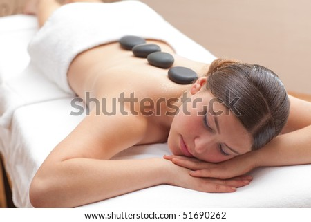 Beautiful young woman enjoying a hot mineral stone treatment in spa, shallow depth of field, focus on face
