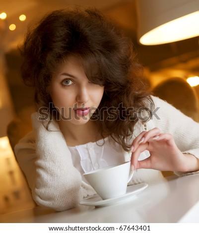 Beautiful young woman enjoying latte coffee in cafe