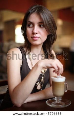 Beautiful young woman enjoying latte coffee in cafe. Shallow DOF.