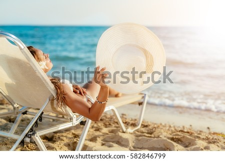 Beautiful young woman enjoying on the beach. She is lying on sunbed, holding summer hat and sunbathing.  #582846799