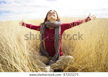 Beautiful young woman enjoying sunshine in a field with long grass