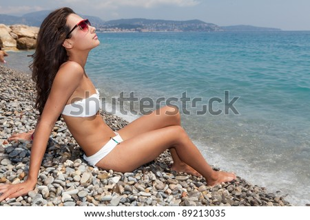 Beautiful young woman enjoying the Mediterranean beach shoreline in the French Riviera in Nice, France.